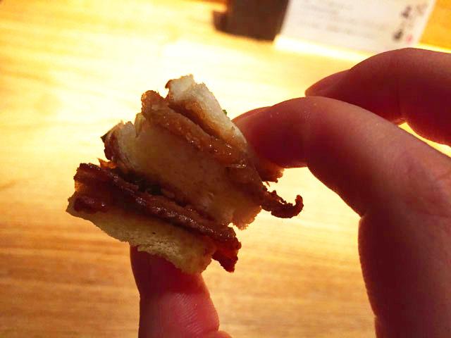 とり皮のサンドイッチを手でつまんで食べようとしているところ