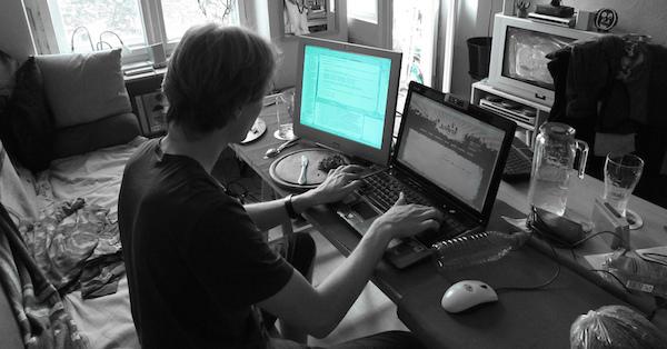 foto de um programador de costas trabalhando em seu notebook com um monitor externo. A foto está tratada para deixar toda a imagem exceto a tela do monitor externo em preto-e-branco.