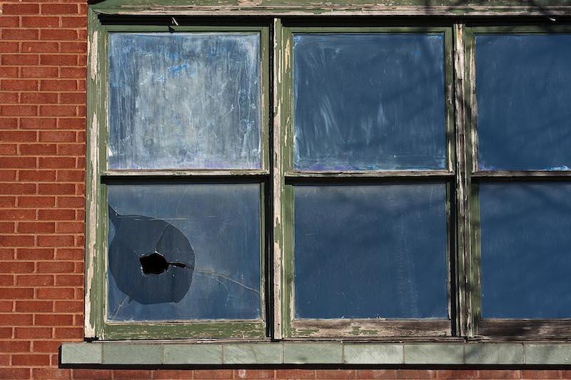 foto de uma janela bem antiga e degradada mas sem nenhum vidro quebrado