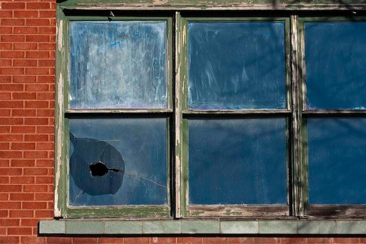 foto de uma janela bem antiga e degradada com um vidro quebrado por uma pedra do lado esquerdo inferior da janela.