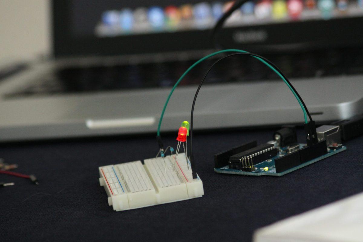 Foto de um Arduino conectado à dois leds em uma placa de prototipação e um macbook pro desfocado ao fundo