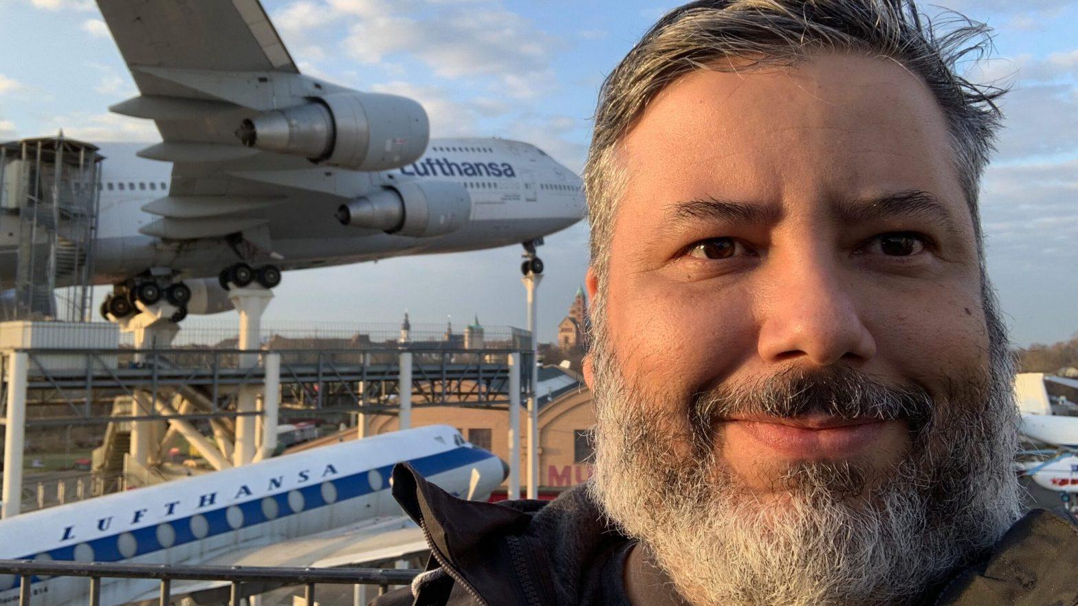 Uma foto minha no museu de tecnologia na Alemanha. Aparece um avião da Lufthansa em exposição no fundo da foto