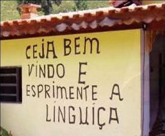 """Foto de uma fachada de restaurante com uma placa escrito: """"Ceja bem vindo e esprimente a linguiça"""""""