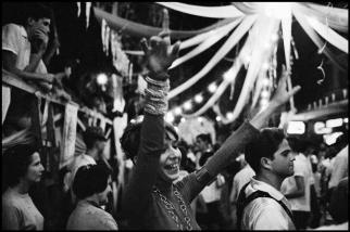 BRAZIL. 1961. Girl wearing beads in carnival crowd.Elliott Erwitt