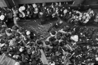 CHINA. Shanghai. Diciembre 1948-enero de 1949. A medida que el valor del papel moneda se hundió, el Kuomintang decidió distribuir 40 gramos de oro por persona. Con la fiebre del oro, en diciembre, miles salieron y esperaron en fila durante horas. Los policías, equipados con los restos de los ejércitos de la Concesión Internacional, no eran crueles, tratando de hacer que la gente volviera. Sólo les salpicaban con el agua sucia del charco.