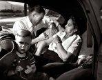 En el asiento trasero de un automóvil, el Dr. Ceriani aplica una inyección de morfina a un turista de 60 años de Chicago, visto aquí con su nieto, que estaba sufriendo una alteración cardiaca menor.