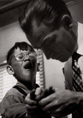 El Dr. Ceriani examina los puntos de la mano lacerada de un paciente joven.