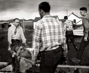 El médico ayuda a un ranchero a llevar a su hijo al hospital. El joven ebrio se dislocó el codo cuando fue echado por caballo salvaje en un rodeo.