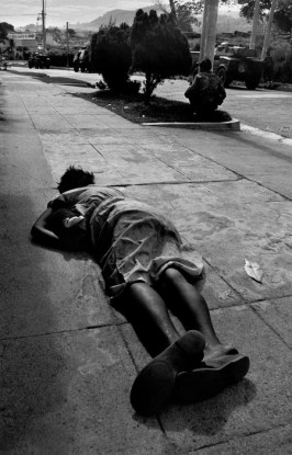 San Salvador. 1989. A dead civilian woman lies on a sidewalk. She had probably been shot for breaking the 6 p.m. to 6 a.m. curfew. In the background, government soldiers move forward to drive guerillas from the capital. Government straffing from the air, armoured personnel carriers, and then foot soldiers eventually drove the FMLN guerillas out.