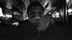 The American author James BALDWIN posing in the lobby of his hotel the Relais Bisson in Paris.