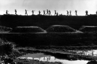 North Vietnam.1969. A bombed dike, North Vietnamese soldiers in active training trot by peasants carrying earth in baskets to fill in the bomb craters from American raids. (RIB.CT.041)