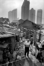 CHINA. Shanghai. Evicted from their homes due to the construction of new skyscrapers, locals live in shanty towns surrounded by fridges, televisions, fans and white goods whilst waiting to be rehoused.