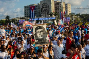 "Cubans file past, one holding a poster that depicts revolutionary hero Ernesto ""Che"" Guevara, in the annual May Day parade at Revolution Square in Havana, Cuba, Tuesday, May 1, 2018. (AP Photo/Desmond Boylan)"