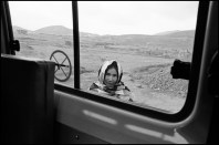 AFGHANISTAN. Kabul. 2011. Child peers into ICRC (International Committee Of The Red Cross) vehicle during home visits to landmine victims and pediatric patients.