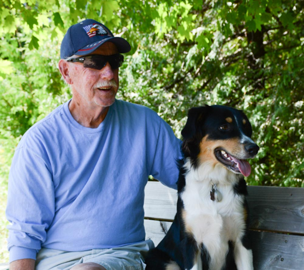 Brian Stubbs and Ollie, frequent users of the Harmony Valley dog park, take a break in the shade. Residents are now calling on the city to create a dog park in the south end of the city.