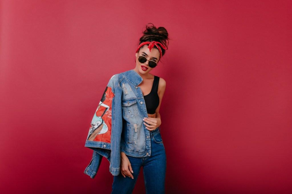빨간색 배경에 똥머리를 묶은 여성이 컨정색 탑 민소매를 입고 청바지를 입은 채 청자켓을 오른쪽 어깨에만 걸친 뒤 선글라스를 끼고 서있는 사진이다.