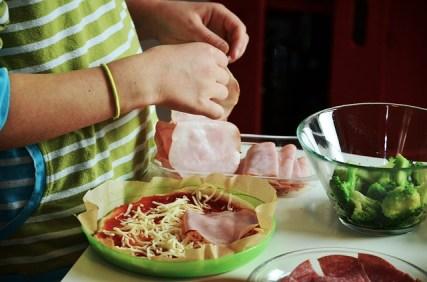 아이가 재료를 이용하여 맛있는 피자나 파스타를 만들고 있는 모습.