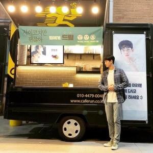 배우 김수현이 선물로 받은 간식차를 인증하기 위해 간식차 옆에 서 있다. 화이트 티셔츠에 체크 무늬 셔츠를 걸쳐 캐주얼한 레이어드 룩을 선보였다.