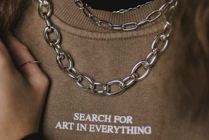 faceless stylish woman in chain necklace and sweatshirt