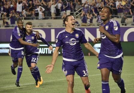 Kevin Molino (left), Antonio Nocerino (middle left) and Adrian Winter (middle right) cheer on Cyle Larin (right) following Orlando City's lone goal against the Chicago Fire in the Orlando Citrus Bowl on Friday, March 11, 2016. The match concluded in a 1-1 draw. (Victor Ng / Orlando Soccer Journal)
