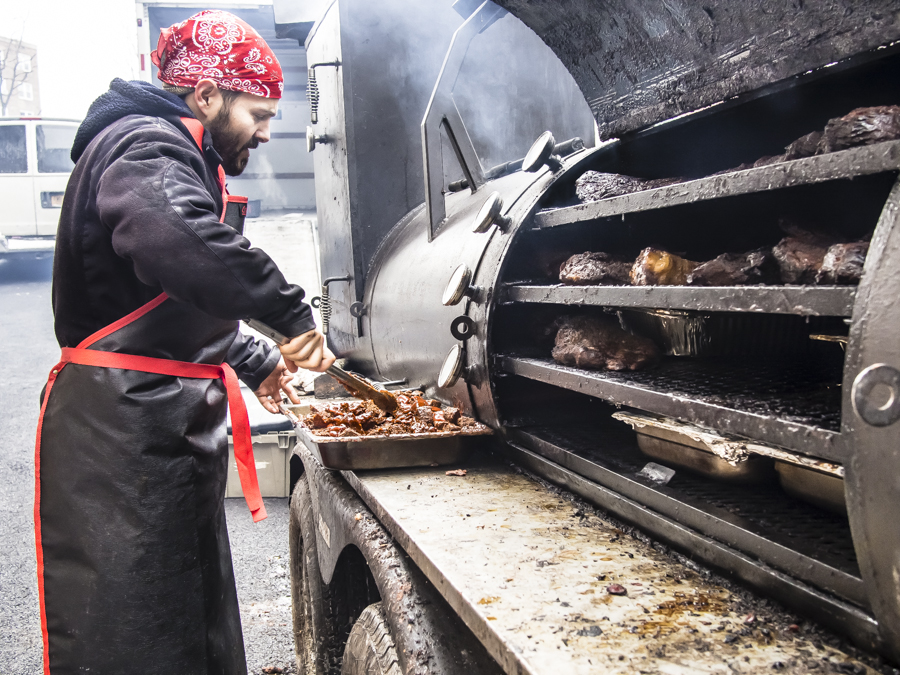 GEMSTONE TRAVELING TEXAS Kosher BBQ Pitboss Ari White stirs the pulled barbeque brisket at their outdoor mobile wood-burning smokehouse at the Bayit Hebrew Institute.