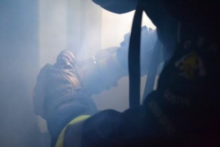 Strażak z prądownicą w zadymieniu
