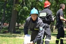 Członek MDP Gostyń w trakcie rozwijania węża pożarniczego