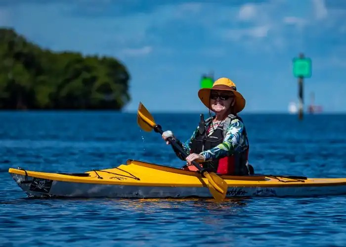 Lady paddling an Eddyline sandpiper on tampa bay with mangrove island in background.