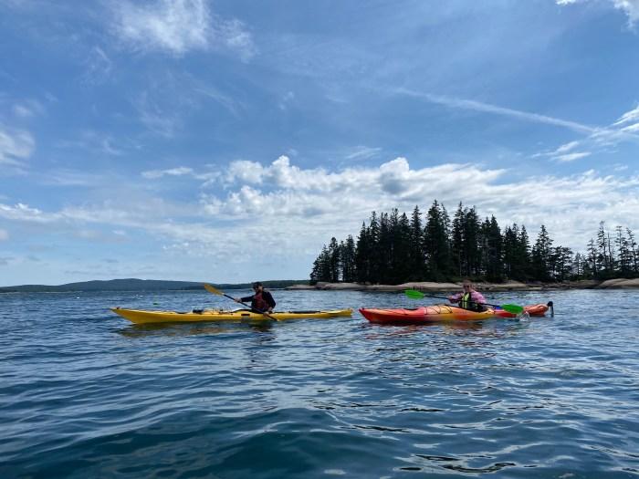 single kayakers go past islands at stonington archipelago
