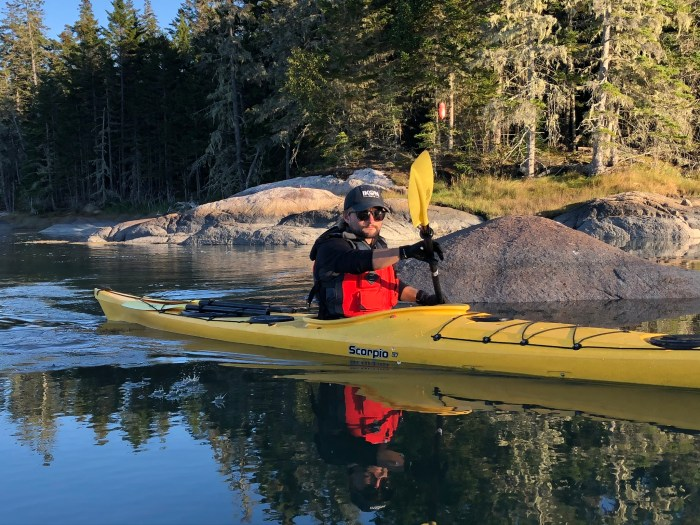 Will Steinharter is a licensed ACA Level 2 sea kayaking guide from Stonington, Maine. He is paddling in a yellow kayak in Webb Cove.