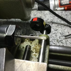 To start, I mounted an appropriate size straighte chucking reamer in the lathe head stock collet. The diameter chosen should completely ream the length of the original ocatave key hinge tube leaving a smooth, even diameter hole from end to end.
