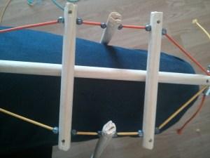Attache des billes de plomb sur les élastiques pour fixer les tiges de bois.