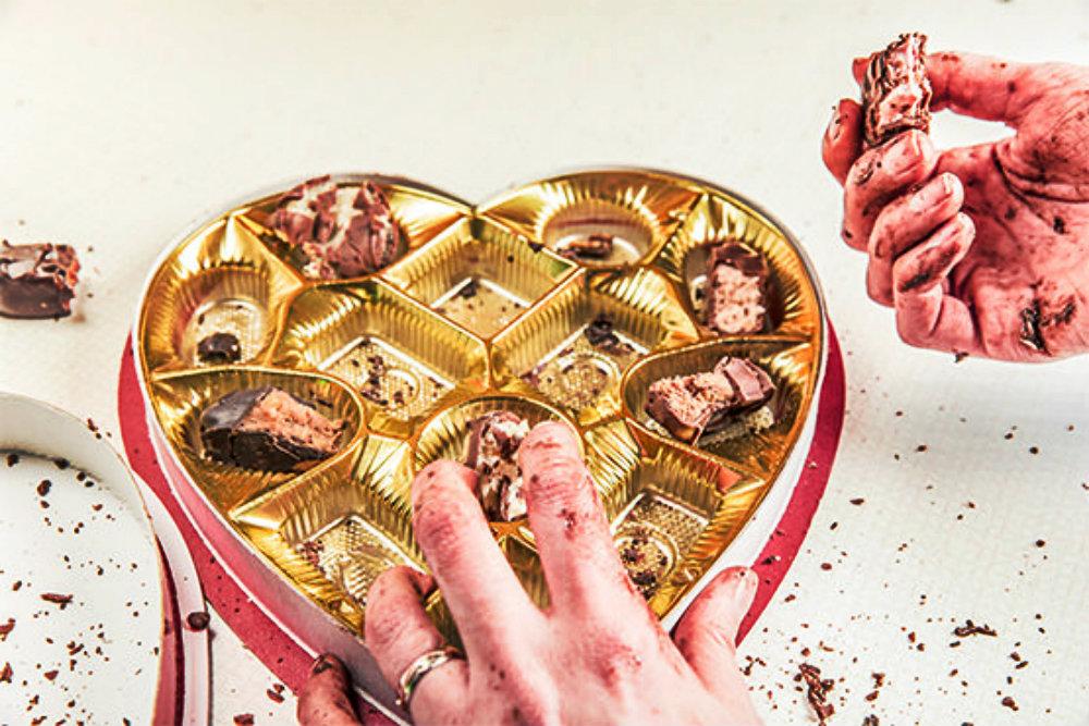 Photos de mains pleines de chocolat devant une boîte illustrant les excès alimentaires des fêtes de fin d'année.