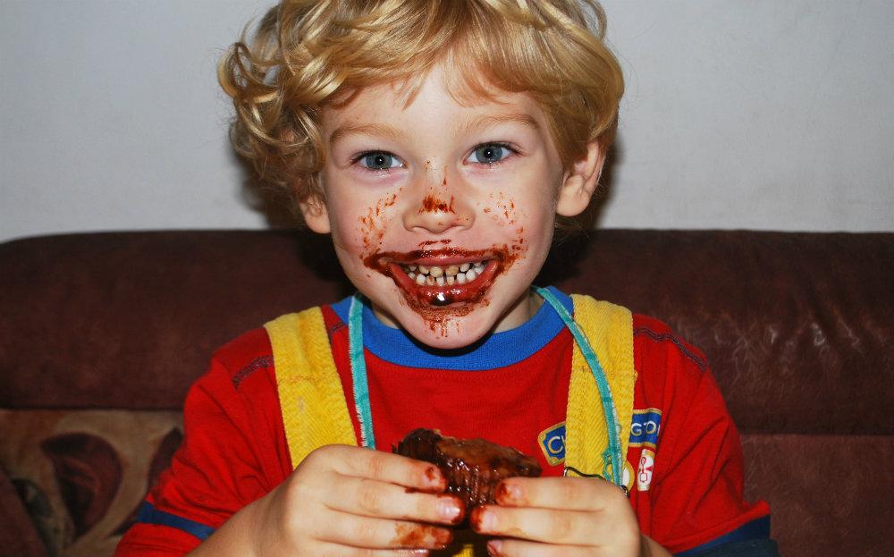 Photo d'un enfant qui mange un gâteau au chocolat, avec du chocolat étalé autour de la bouche. La digestion humaine se fait dans le tube digestif, pas sur la peau !