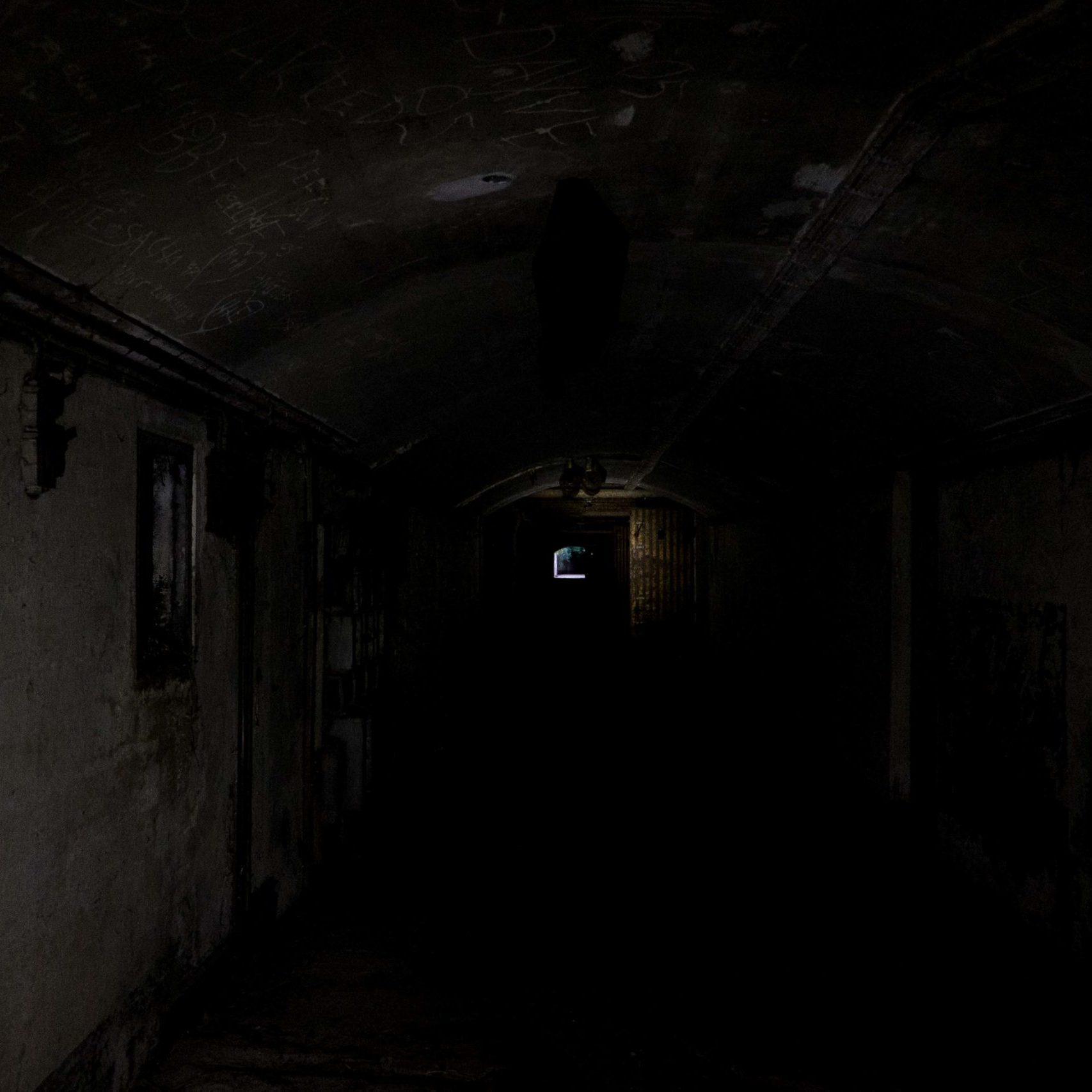 Flakfortet: dunkler, unbeleuchteter Gang, am Ende des Gangs sieht man Tageslicht