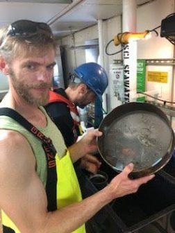 Man holding a metal seine dish