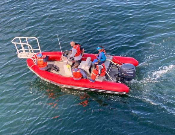 Four people in the red rigid hull inflatable boat
