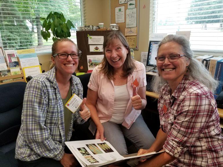 Three OSU Extension Master Gardener volunteers are all smiles while volunteering in the Clackamas Co. Master Gardener helpline office.