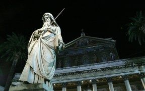 STATUE ILLUMINATED IN NIGHT VIEW OF BASILICA OF ST. PAUL OUTSIDE THE WALLS IN ROME