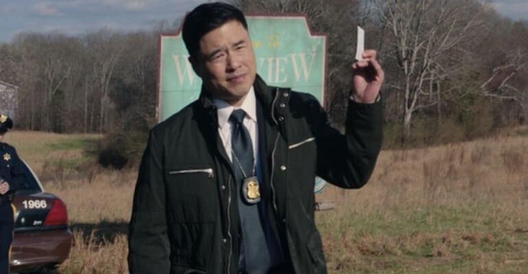 Jimmy Woo levantando um papel na frente da placa de Westview em WandaVision