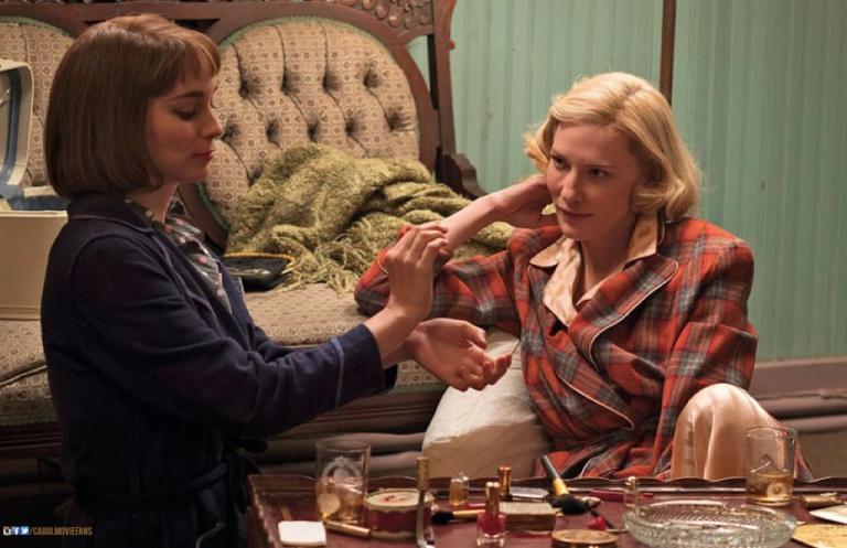 Duas mulheres sentadas experimentando um perfume