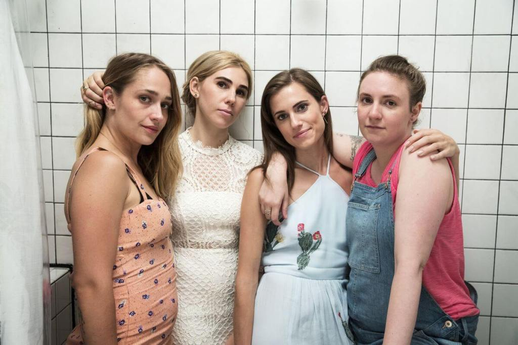 Quatro mulheres abraçadas em um banheiro