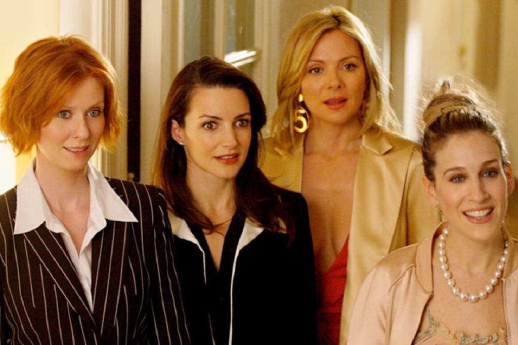 Quatro mulheres usando roupas diferentes e surpresas olhando para alguém