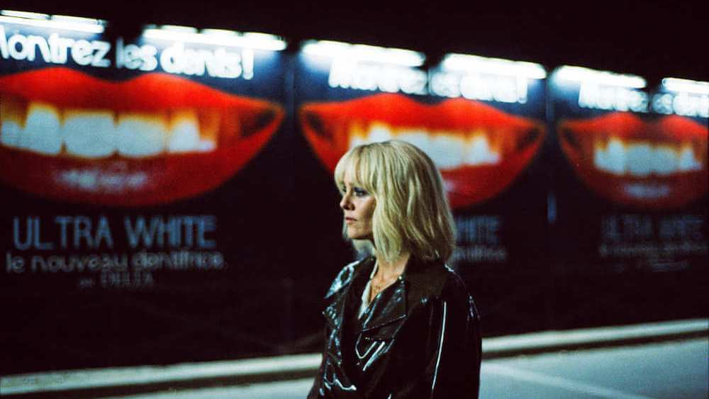 Mulher loira parada na frente de vários cartazes com uma boca no centro