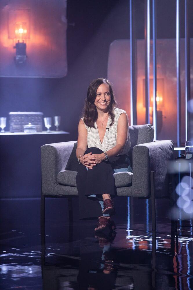 Atriz Lauren Hissrich, de The Witcher, sentada em poltrona cinza, de lado, com pernas cruzadas, sorrindo. Veste um camisa branca de poá e calças pretas - Otageek