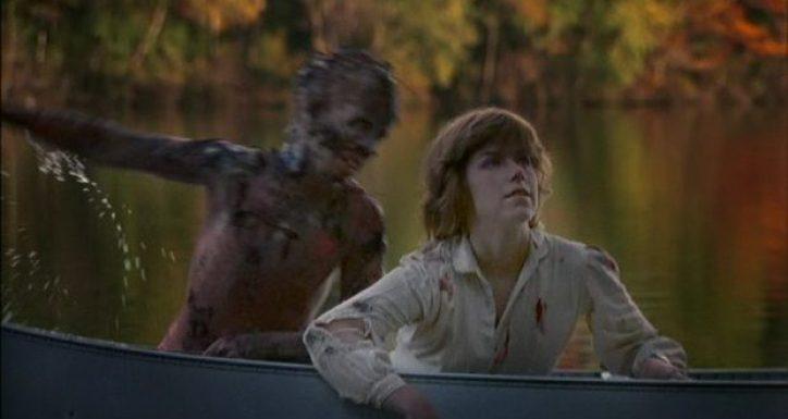 Mulher deitada em um barco enquanto um garoto deformado e pelado tenta puxá-la nesse clássico de terror dos anos 80