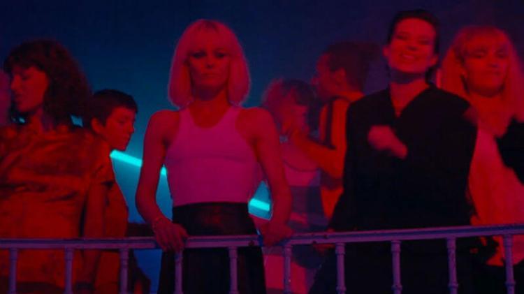 Mulher com camisa branca parada sob a luz neon