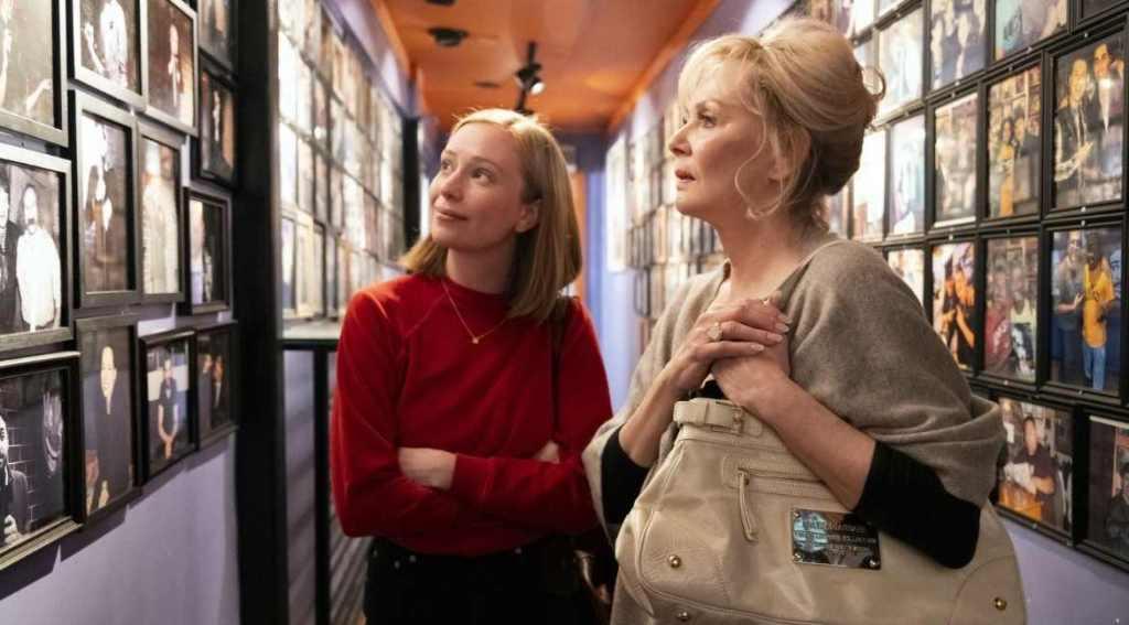 """Cena da série, onde temos Ava, de suéter vermelho e Deborah, de cardigã bege, as duas olham para uma parede cheia de fotos no seriado """"Hacks""""."""