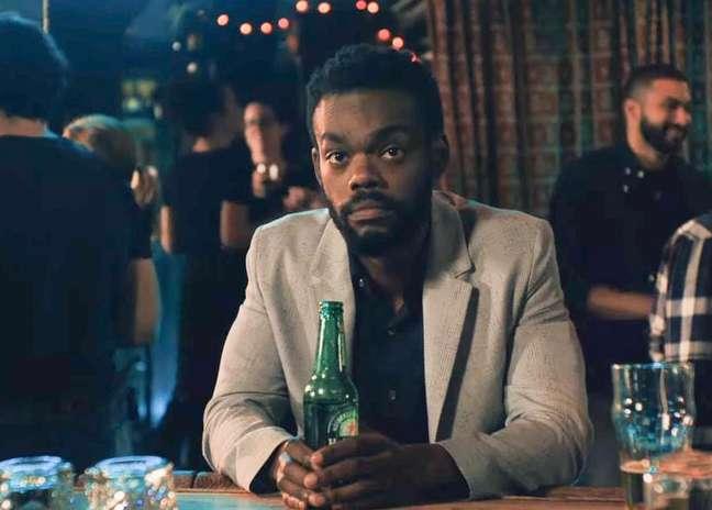homem negro de terno claro, sentado em uma mesa com uma garrafa de cerveja em mãos