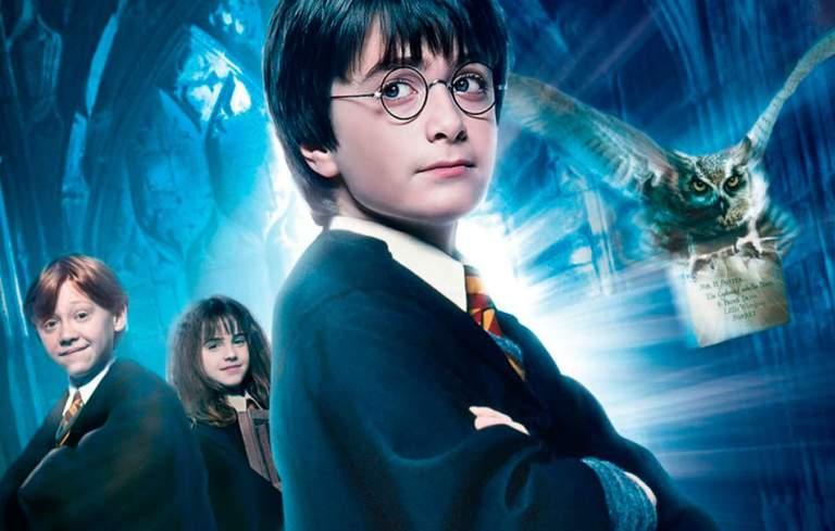 Poster do filme Harry Potter e a Pedra filosofal, mostrando Harry na frente, Ron e Hermione atrás dele, enquanto Hedwig voando a esquerda